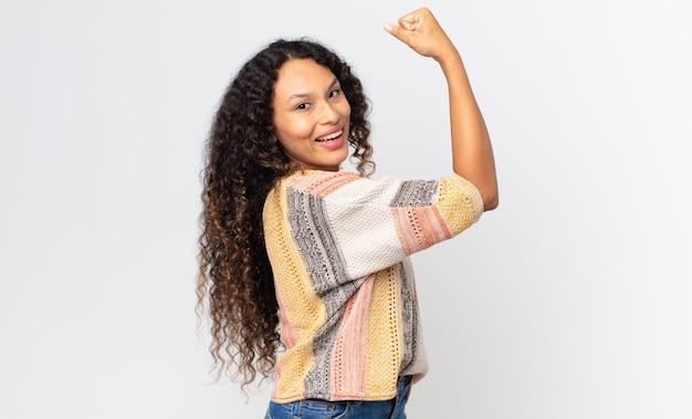 Bella donna ispanica che si sente felice, soddisfatta e potente, si flette in forma e bicipiti muscolari, sembra forte dopo la palestra