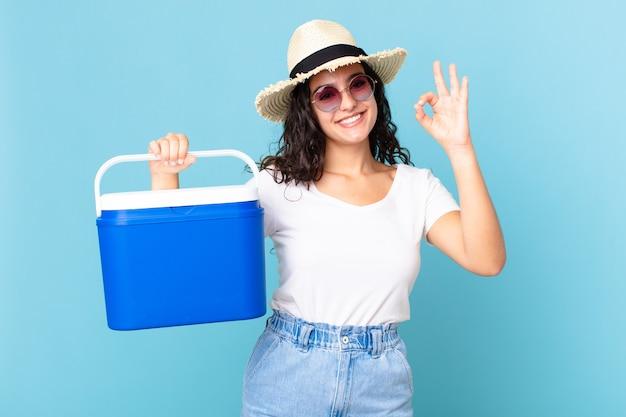 Bella donna ispanica che si sente felice, mostra approvazione con un gesto ok che tiene in mano un frigorifero portatile