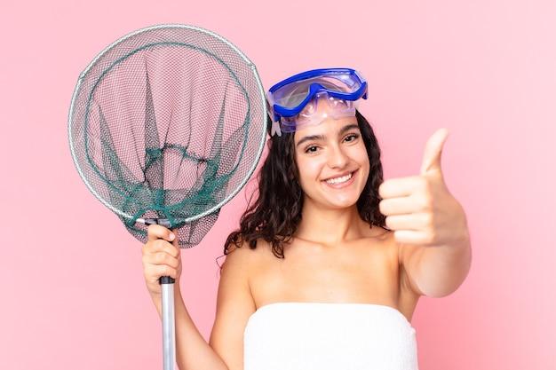 Bella donna ispanica che si sente orgogliosa, sorride positivamente con il pollice in alto con gli occhiali e la rete da pesca
