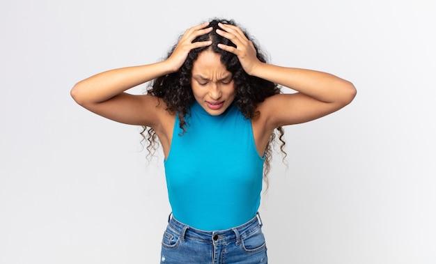 Bella donna ispanica che si sente stressata e frustrata, alza le mani alla testa, si sente stanca, infelice e con emicrania
