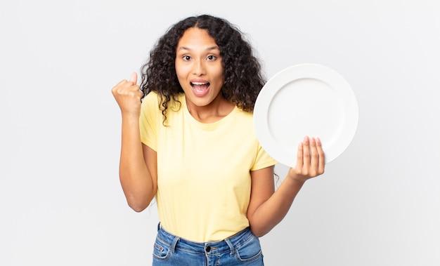 Bella donna ispanica con in mano un piatto pulito e vuoto