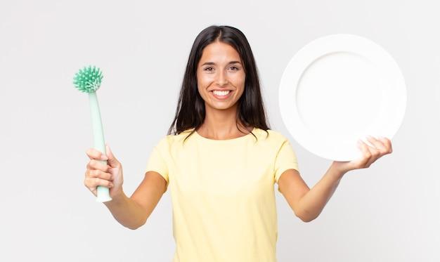 Bella donna ispanica che tiene un piatto pulito epty