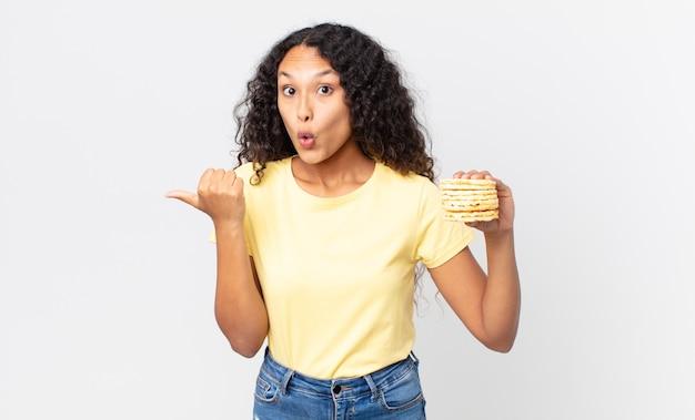 Bella donna ispanica che tiene in mano una torta dietetica di riso?