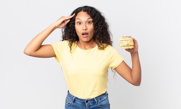 Bella donna ispanica che tiene una torta dietetica di riso?