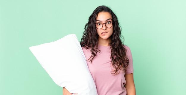 Bella donna ispanica che sembra perplessa e confusa e indossa un pigiama con un cuscino