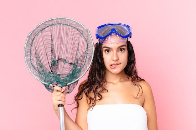 Bella donna ispanica che sembra perplessa e confusa con gli occhiali e la rete da pesca