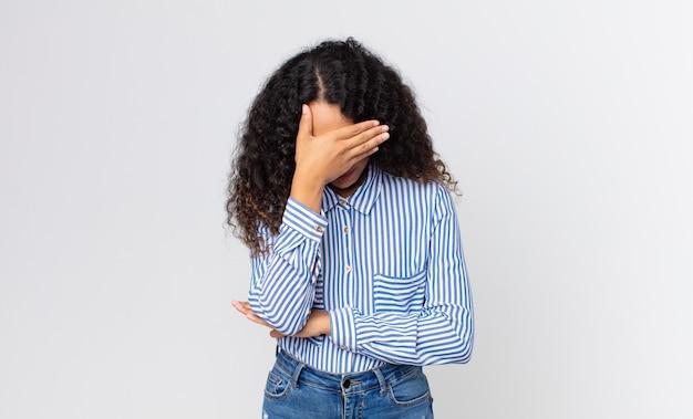 Bella donna ispanica che sembra stressata, imbarazzata o turbata, con mal di testa, che copre il viso con la mano