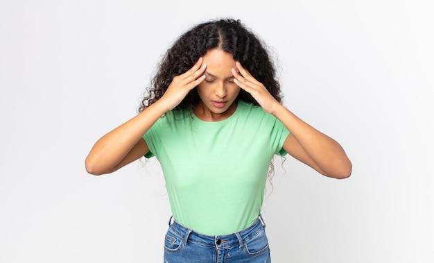 Bella donna ispanica che sembra stressata e frustrata, lavora sotto pressione con mal di testa e turbata da problemi