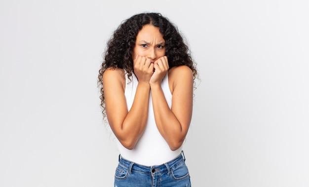 Bella donna ispanica che sembra preoccupata, ansiosa, stressata e impaurita, si morde le unghie e guarda allo spazio laterale della copia
