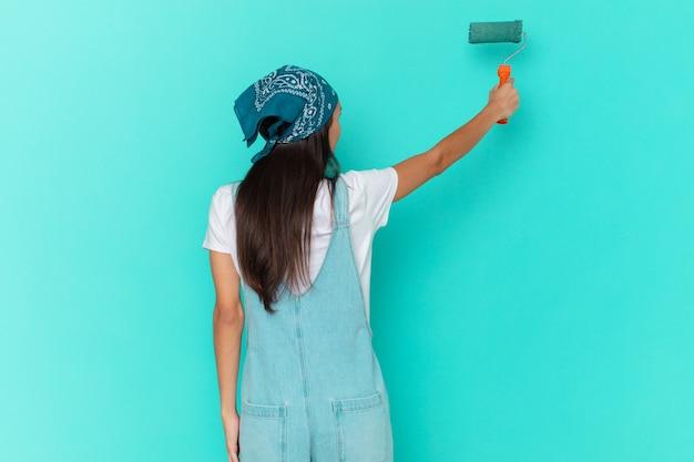 Bella donna ispanica che dipinge un muro