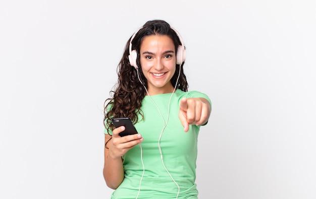 Bella donna ispanica che punta alla telecamera scegliendo te con le cuffie e uno smartphone