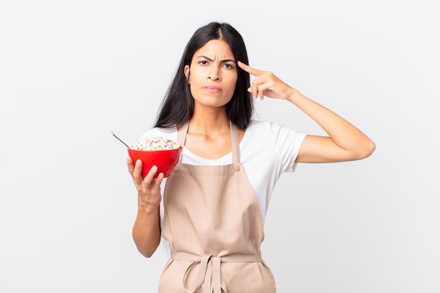 Bella donna ispanica bella chef ispanica che tiene in mano una ciotola di fiocchi