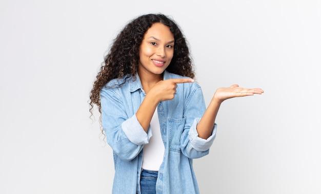Bella donna ispanica che sorride allegramente e indica lo spazio della copia sul palmo sul lato, mostrando o pubblicizzando un oggetto