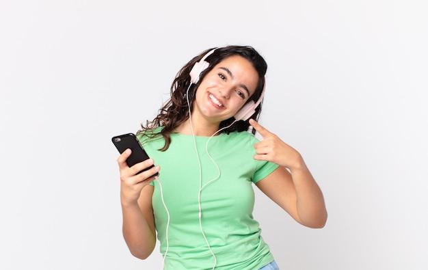 Bella donna ispanica che sorride con sicurezza indicando il proprio ampio sorriso con le cuffie e uno smartphone