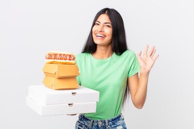 Bella donna ispanica che sorride felicemente, agitando la mano, accogliendoti e salutandoti e tenendo in mano scatole di fast food da asporto