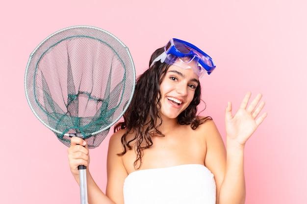 Bella donna ispanica che sorride felicemente, agitando la mano, accogliendoti e salutandoti con occhiali e rete da pesca
