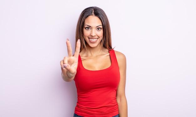 Bella donna ispanica che sorride e sembra amichevole, mostrando il numero due o il secondo con la mano in avanti, conto alla rovescia