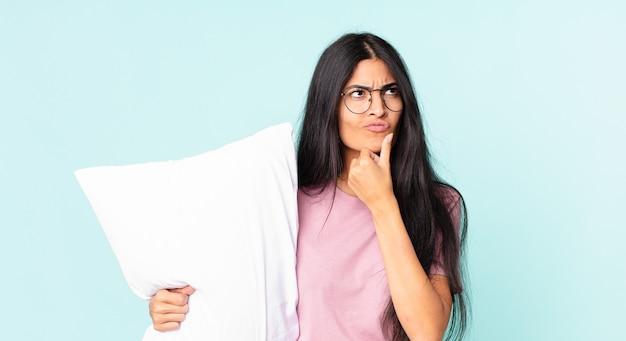 Bella donna ispanica che pensa, si sente dubbiosa e confusa e indossa un pigiama con un cuscino