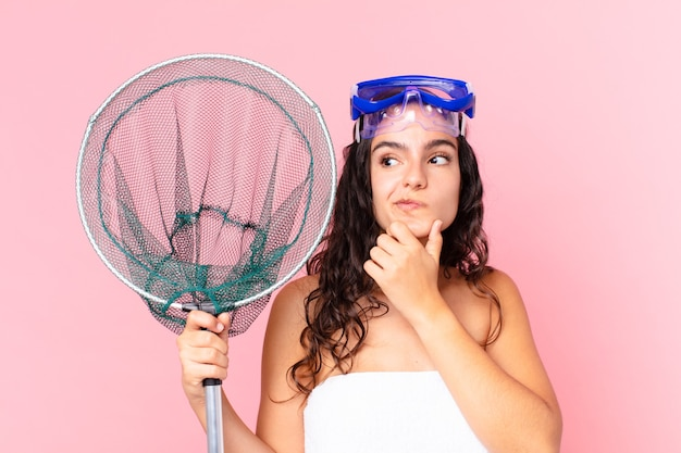 Bella donna ispanica che pensa, si sente dubbiosa e confusa con gli occhiali e la rete da pesca