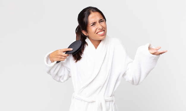 Bella donna ispanica che indossa accappatoio e tiene in mano una spazzola per capelli