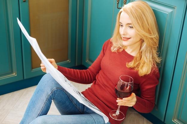 Giovane donna bionda piuttosto ispirata che sorride e legge un giornale e tiene un bicchiere di buon vino rosso mentre è seduto sul pavimento