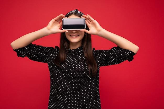 Condizione della ragazza castana felice abbastanza gioiosa isolata sopra la parete rossa che indossa vestiti neri alla moda casuali che mostrano mobile