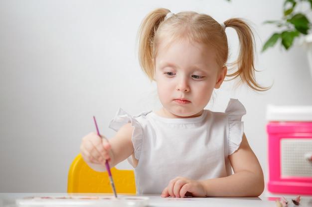 Ragazza graziosa del bambino che dipinge con gli acquerelli a casa