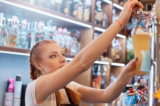 Bella signora barista con un bicchiere di birra al lavoro, barista toccando bevanda alcolica