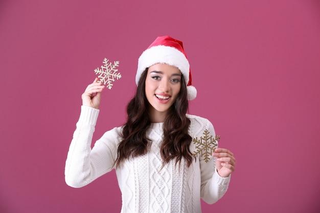 Bella signora con cappello di natale che tiene i fiocchi di neve su uno sfondo colorato