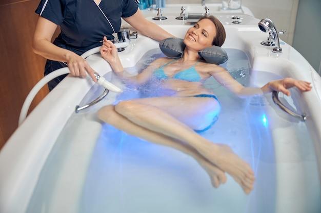 Bella signora sdraiata su un cuscino per il collo nella vasca da bagno durante il massaggio della doccia subacquea