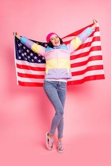 Bella signora che fa le foto con la bandiera degli stati uniti felice di visitare il nuovo paese indossare un cappotto colorato caldo isolato su sfondo rosa