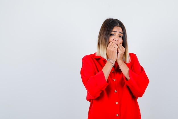 Bella signora in camicetta rossa che si tiene per mano sulla bocca e sembra spaventata, vista frontale.