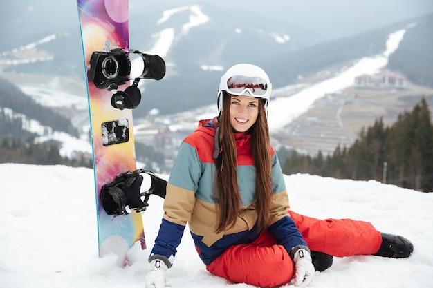 Bella signora snowboarder sulle piste gelida giornata invernale