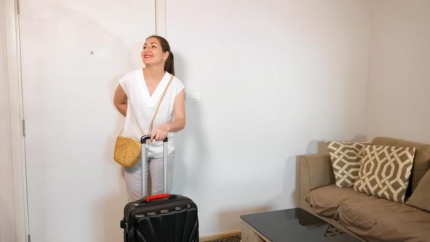 La bella signora con la coda di cavallo entra nella stanza d'albergo portando una grande valigia e sorride guardandosi intorno vicino al divano marrone