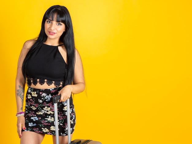 Bella donna latina, con la valigia, su sfondo giallo