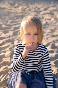 Ragazza graziosa del bambino con gli occhi azzurri in maglietta a strisce che guarda l'obbiettivo, succhiando lecca-lecca