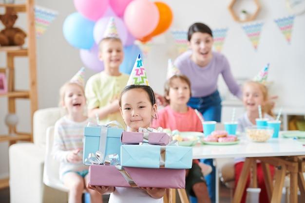 Bambina graziosa nel cappello di compleanno che tiene pila di regali estatici amici e madre divertendosi a casa festa
