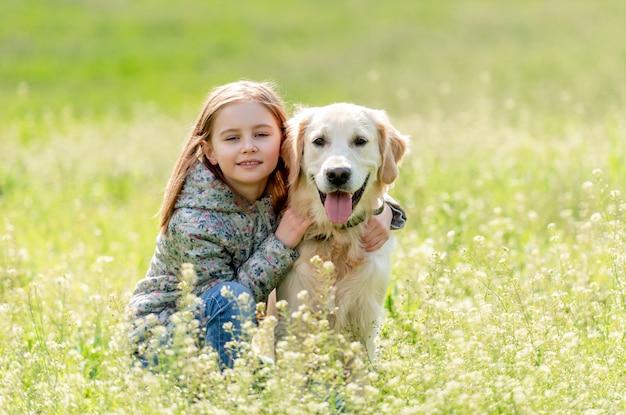 Cane grazioso d'abbraccio della bambina graziosa