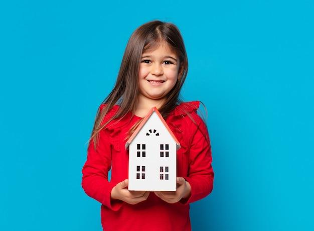 Bella bambina felice espressione e in possesso di un modello di casa