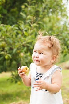 Bambina graziosa che tiene una mela in mano, in piedi sotto il melo