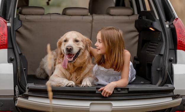Bambina graziosa che abbraccia il cane del documentalista dorato e che si trova insieme nel bagagliaio dell'auto. bambino carino che riposa con un cagnolino nel veicolo