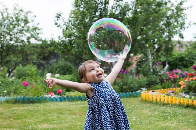 La bambina graziosa sta giocando con le grandi bolle in un parco.