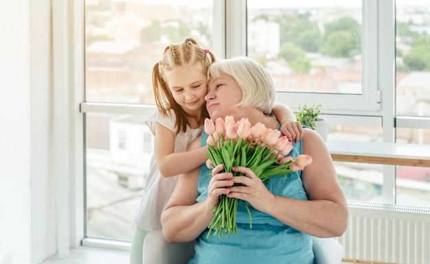 Bambina graziosa che bacia nonna felice
