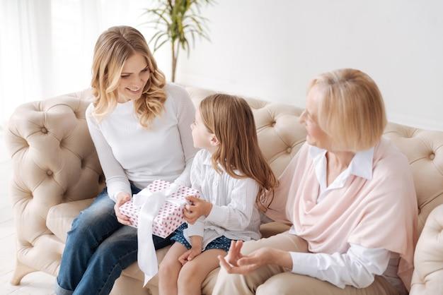 Bambina graziosa che passa una confezione regalo legata con un nastro bianco a sua madre mentre sua nonna osserva questo processo