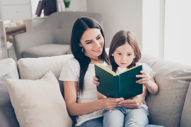 La bambina graziosa ha letto il libro interessante con la sua mamma nella casa domestica interna
