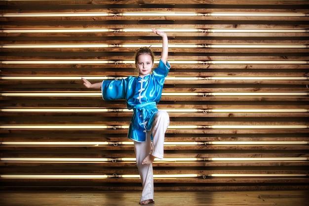 La graziosa bambina nella stanza in abbigliamento sportivo per arti marziali è wushu o kung fu