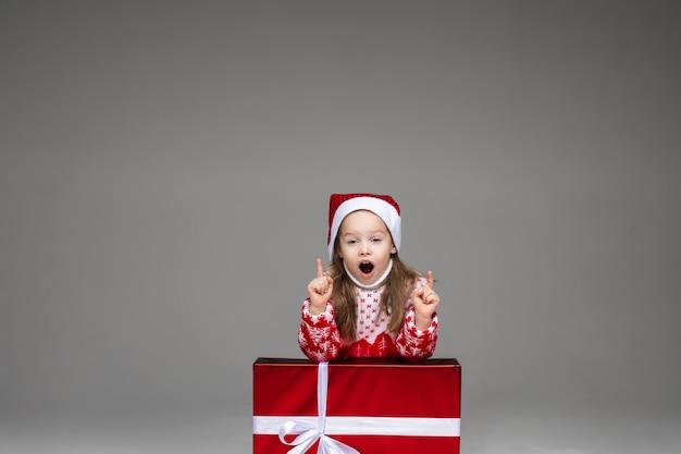 Bambina graziosa in cappello della santa e maglione invernale che annuncia informazioni con le dita appoggiate al regalo di natale. isoolate sul muro grigio.