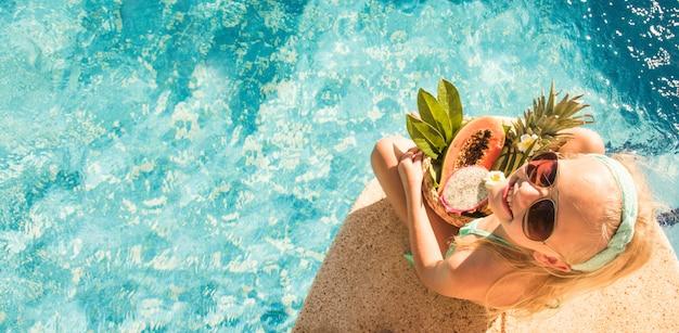 Bambina graziosa in piscina, vacanze estive.