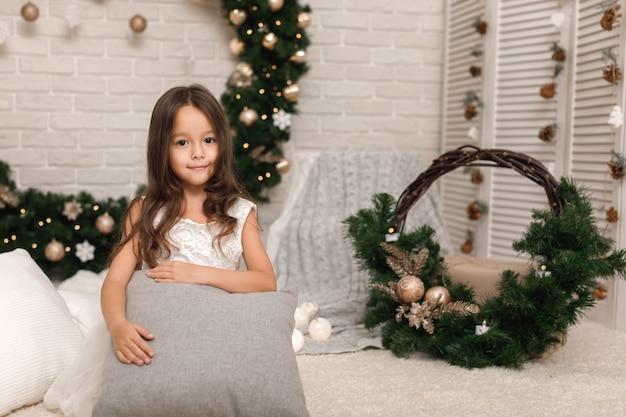 Bambina graziosa in un vestito bianco a natale
