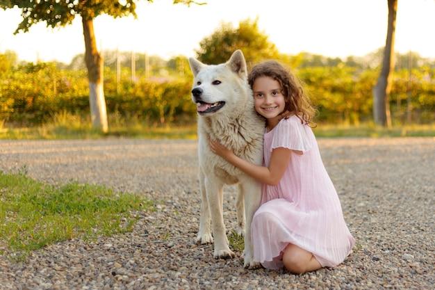 Bambina graziosa con un grosso cane bianco nel parco. una bella bambina di 7 anni in abito rosa abbraccia il suo cane preferito durante una passeggiata estiva.